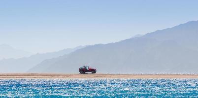 röd jeep på stranden