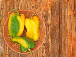 gröna och gula paprika på en korgplatta på en träbordbakgrund foto