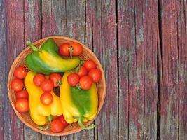 gröna och gula paprika och tomater på en korgplatta på en träbordbakgrund foto
