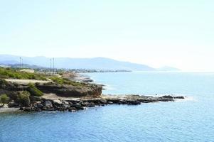 vacker blå lagun med klart havsvatten och en stenstrand och stenar foto