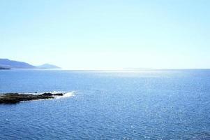 marinmålning med berg och stenar vid gryningen, vackert blått vatten och himmel foto