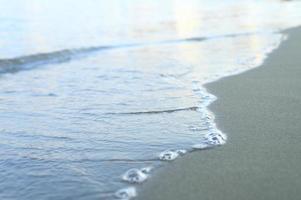suddig våg av havet på kvällen sandstranden