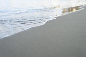suddig våg av havet på kvällen sandstranden foto