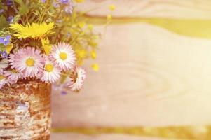 en bukett vildblommor med glömma mig, prästkragar och gula maskrosor i full blom i en rustik burk foto