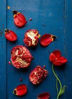 röd tulpan och granatäpple med frön på mörkblå träbakgrund, platt layout foto