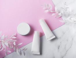 vita rör med grädde på en marmor och rosa bakgrund foto