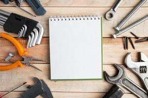 uppsättning arbetsredskap med ett anteckningsblock på en träbakgrund foto