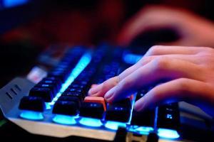närbild på mänskliga händer på ett neonbelyst tangentbord foto