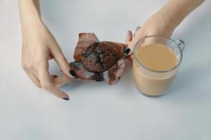 kvinnans händer packar upp en chokladmuffin foto