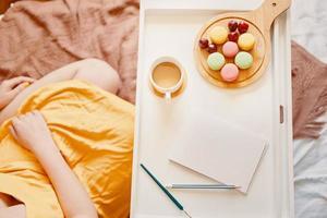 flicka i gul klänning som sitter på sängen med bricka med kaffe, efterrätt och tom anteckningsbok foto