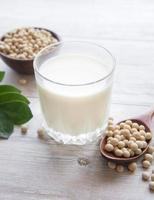 sojamjölk och soja på ett träbord foto
