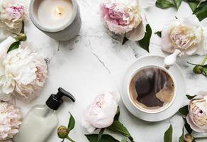 rosa pionblommor och en kopp kaffe foto