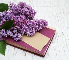 lila blommor och en gammal bok med ett kort på en träbakgrund foto