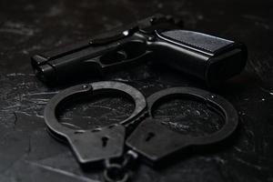 pistol och handbojor på svart texturerat bord