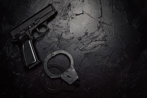 pistol och handbojor på svart texturerat bord foto