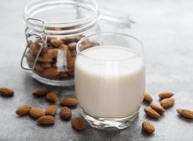glasflaska med mandelmjölk och mandlar på bordet foto