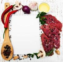 köttbiffar, en receptbok och ingredienser på en gammal träbakgrund foto