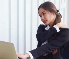 asiatisk kvinna på kontoret har smärta på grund av långa timmar av sittande foto