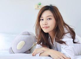 vacker asiatisk kvinna som ler i sängen på semester foto