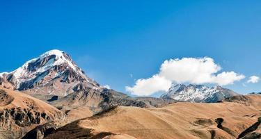 höga klippor och berg med snö på toppar i Georgien foto