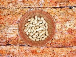 hela jordnötter i en flätad skål på en träbordbakgrund foto