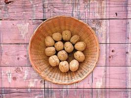 hela valnötter i en flätad skål på en träbordbakgrund foto