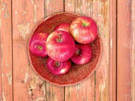 röda äpplen på en korgplatta på en träbordbakgrund foto