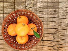 apelsiner i en flätad skål på en träbordbakgrund foto
