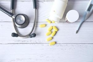 stetoskop och pillerbehållare på träbakgrund
