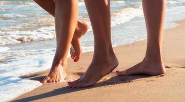 två människors fötter i sand foto