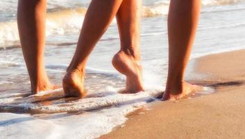 två personer som går med bara fötter på sand foto