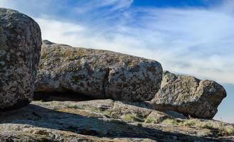 stora stenar mot en blå himmel och vita moln foto