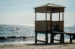 trä lusthus på styltor på stranden foto
