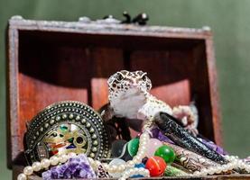prickig eublefar sitter på en hög med smycken i en dekorativ bröstkorg foto