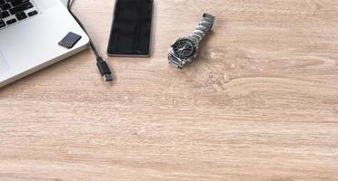 klocka, mobiltelefon och bärbar dator på ett bord foto