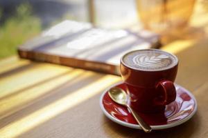 närbild av varm konst latte, cappuccino kaffe i en röd kopp på ett träbord i ett kafé med en suddig bakgrund foto