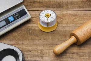 bageri- och matlagningsverktyg med en köketimer, våg och köksform på ett träbord