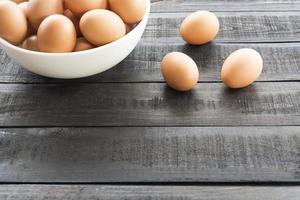 kycklingägg i en vit skål och tre kycklingägg utanför på ett svart träbord