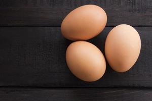 tre färska kycklingägg på ett träbord
