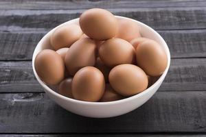 färska kycklingägg i en vit skål på ett svart träbord