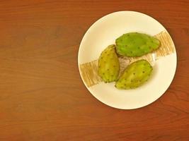 taggiga päron på en keramisk platta på en träbordbakgrund foto