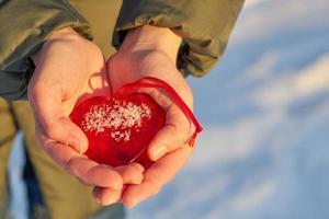 rött glashjärta i händerna foto