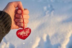rött hjärta i hand med snö foto