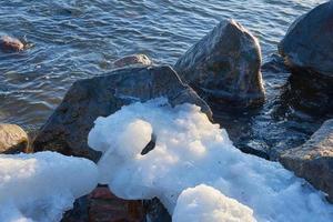 stenar och is vid kusten foto