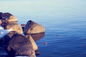 blått vatten med is på stenar foto