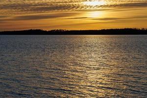 gyllene solljus på vatten foto