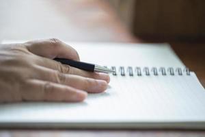 närbild av en hand som håller en penna med en anteckningsbok foto