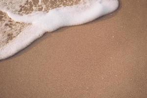 ovanifrån av sand och havsvattenstänk med kopieringsutrymme på en tropisk ren sommarstrand foto