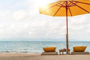 paraply och stol på en tropisk sommarstrandbakgrund med blå himmel för kopieringsutrymme foto
