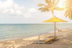 paraply och stol på en tropisk sommarstrandbakgrund med blå himmel för kopieringsutrymme
